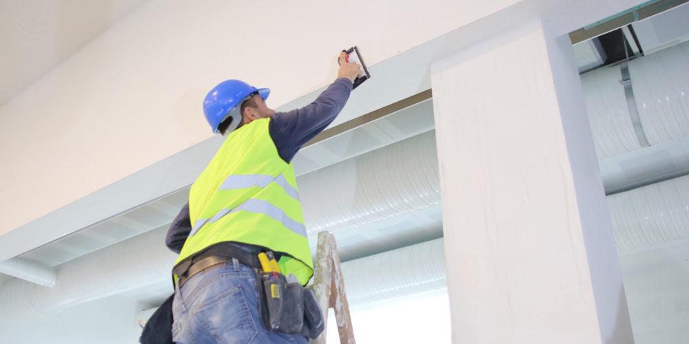 Plaster applying plaster on a new drywall installation.